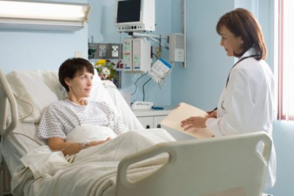 Female doctor talking to female patient lying in hospital bed -- GETTY